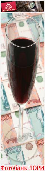 Бокал красного вина на фоне российских банкнот - изображение продается через Фотобанк Лори