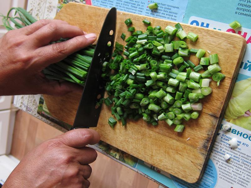 Фотография того, как мелко режутся перья лука для заготовки на зиму