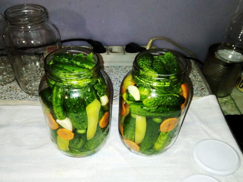 Поделите примерно поровну огурчики и остальные овощи с приправами, чтобы они равномерно заполнили объем стеклотары.