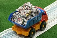 Игрушкчный грузовик перевозит макулатуру по дороге, встланной деньгами, в Фотобанке «Fotolia»
