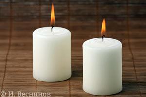 Фотография двух горящих свечей на бамбуковой салфетке