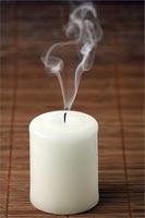 Фотография погасшей свечи на фоне бамбуковой салфетки