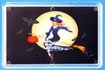 Ведьма-красавица летит на метле на фоне луны.